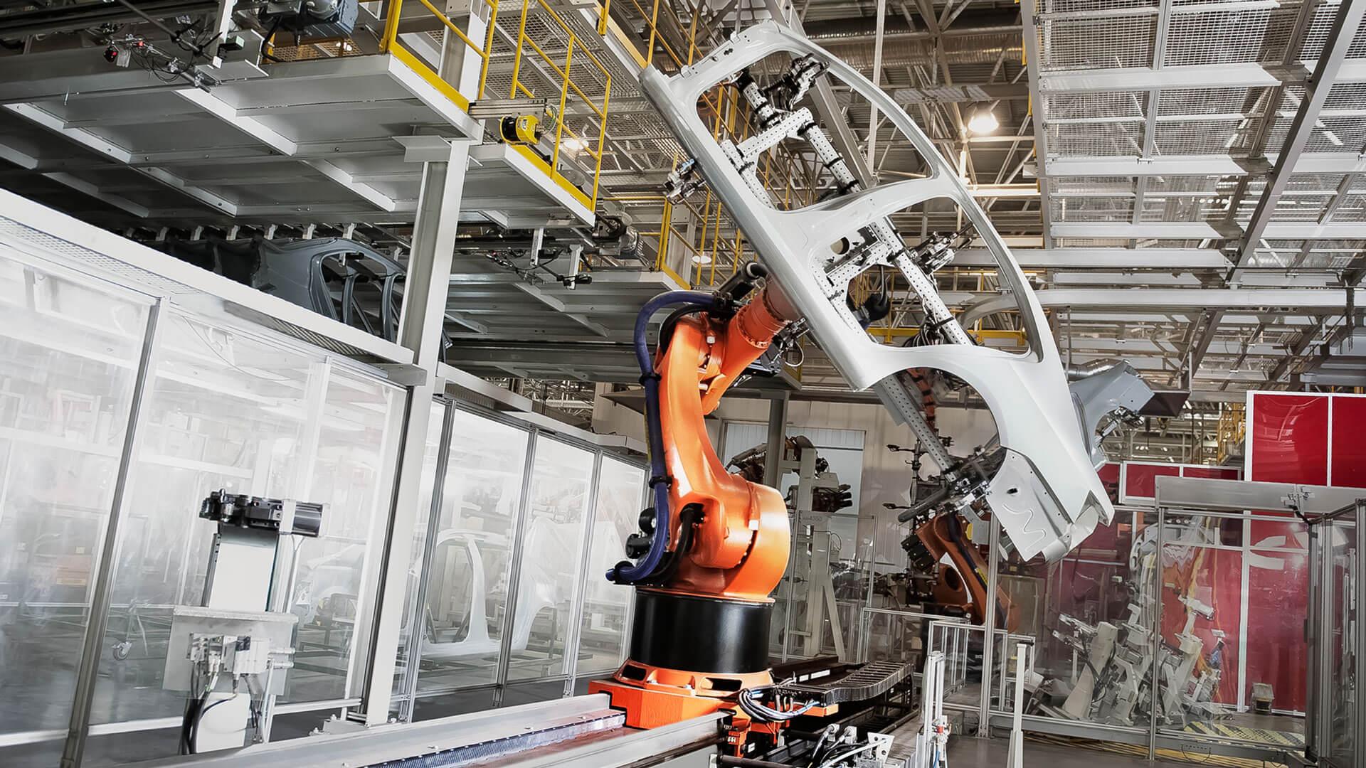 Ein Bild einer Industriehalle, in der Automobile produziert werden. Ein orangefarbener Schwenkarm bewegt gerade ein Autoteil.