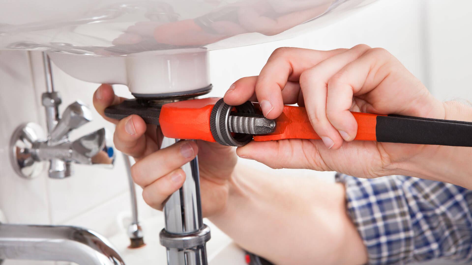 Hausmeister repariert kaputtes Waschbecken mit Schraubenschlüssel