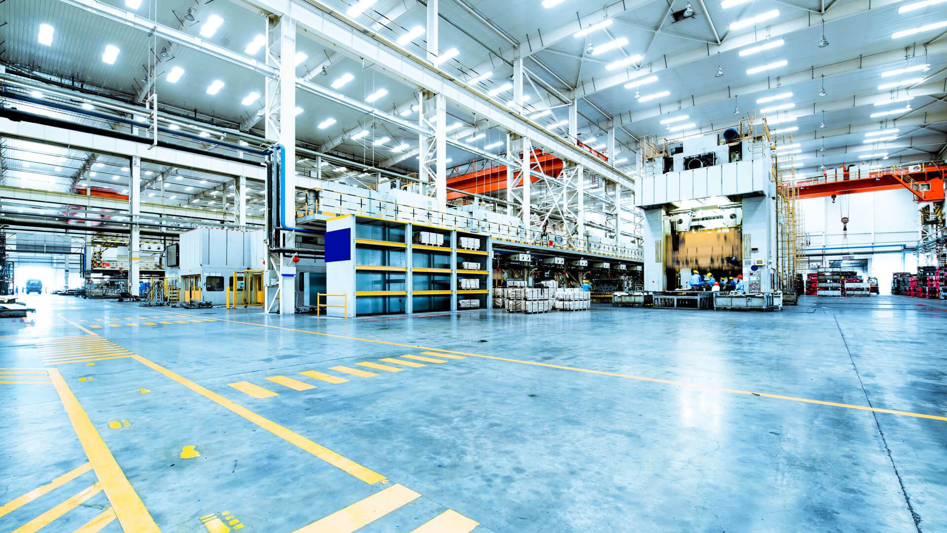 Ein Bild einer industriellen Lagerhalle mit Hochregalen und Maschinen im Hintergrund.