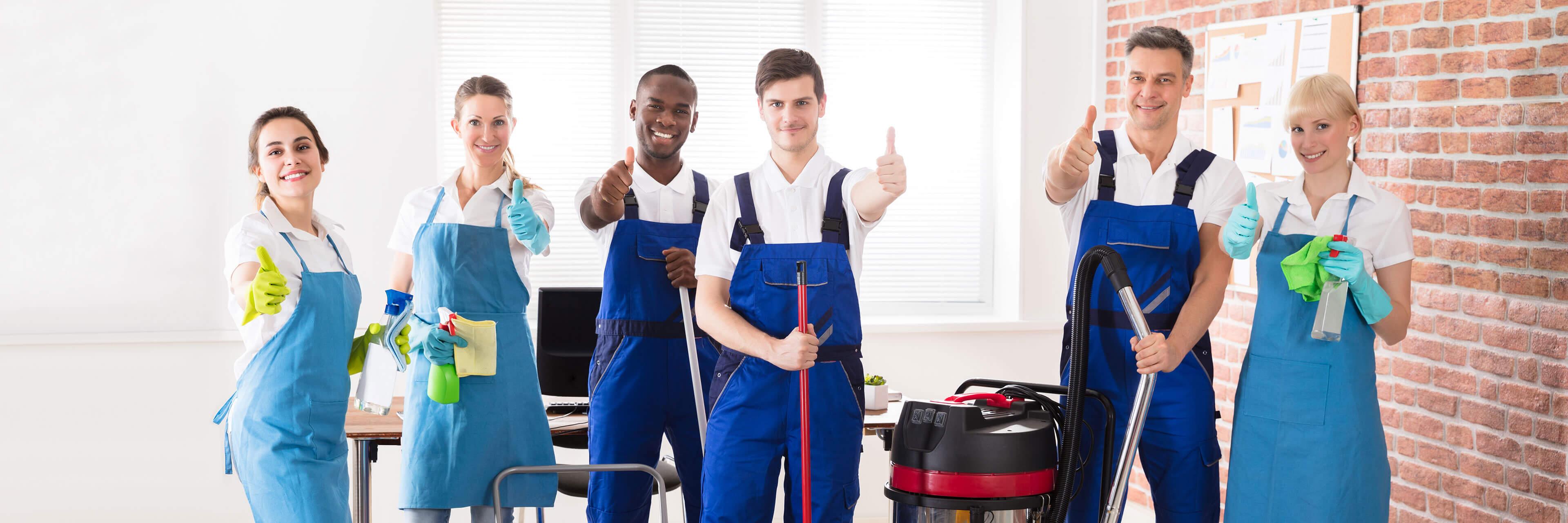 Ein Bild von sechs Reinigungskräften, die in Arbeitskleidung und mit Reinigungsmitteln in den Händen in einem Büro stehen. Dabei heben sie den Daumen nach oben.