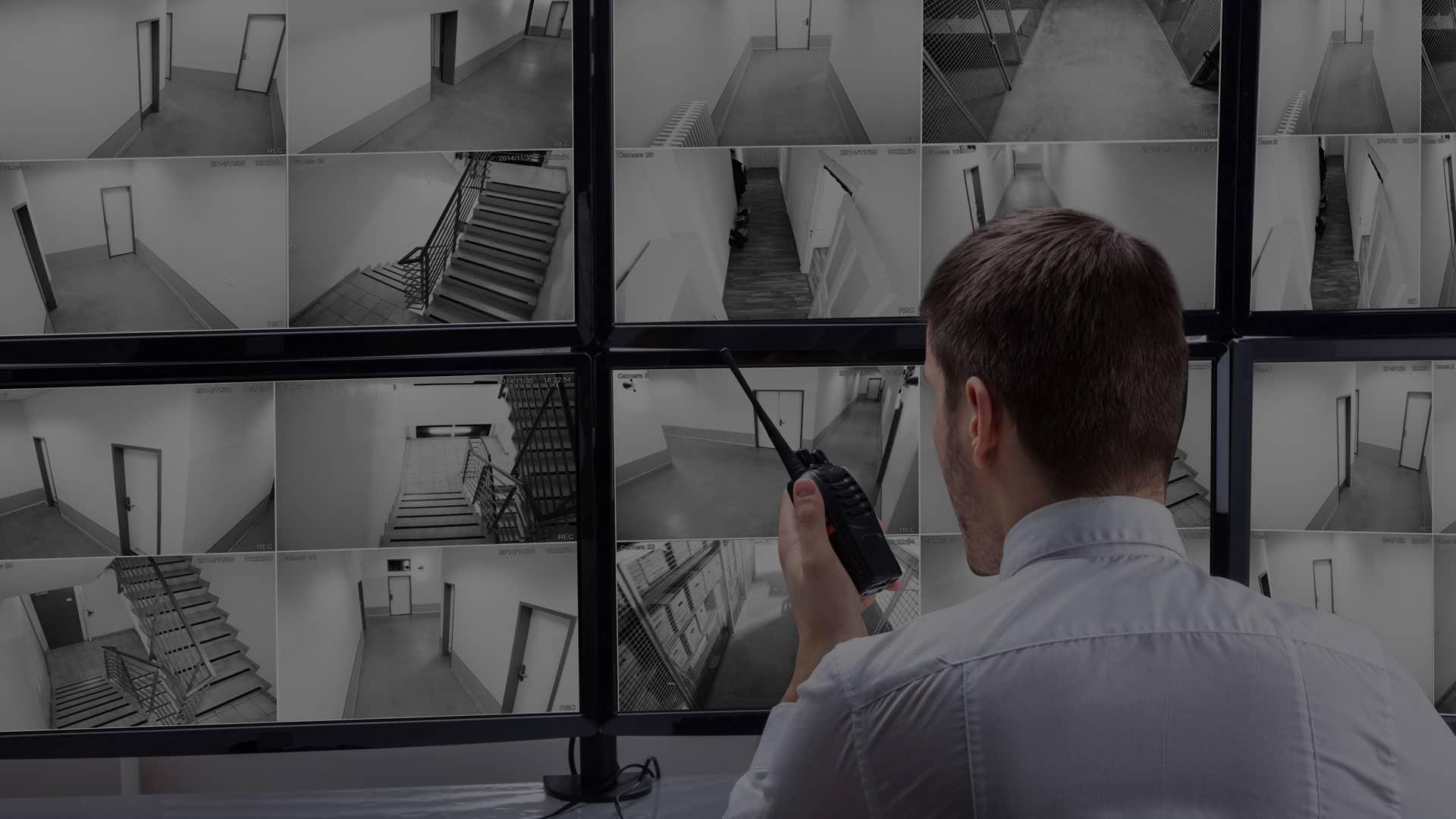 Sicherheitsdienst-Mitarbeiter vor den Bildschirmen