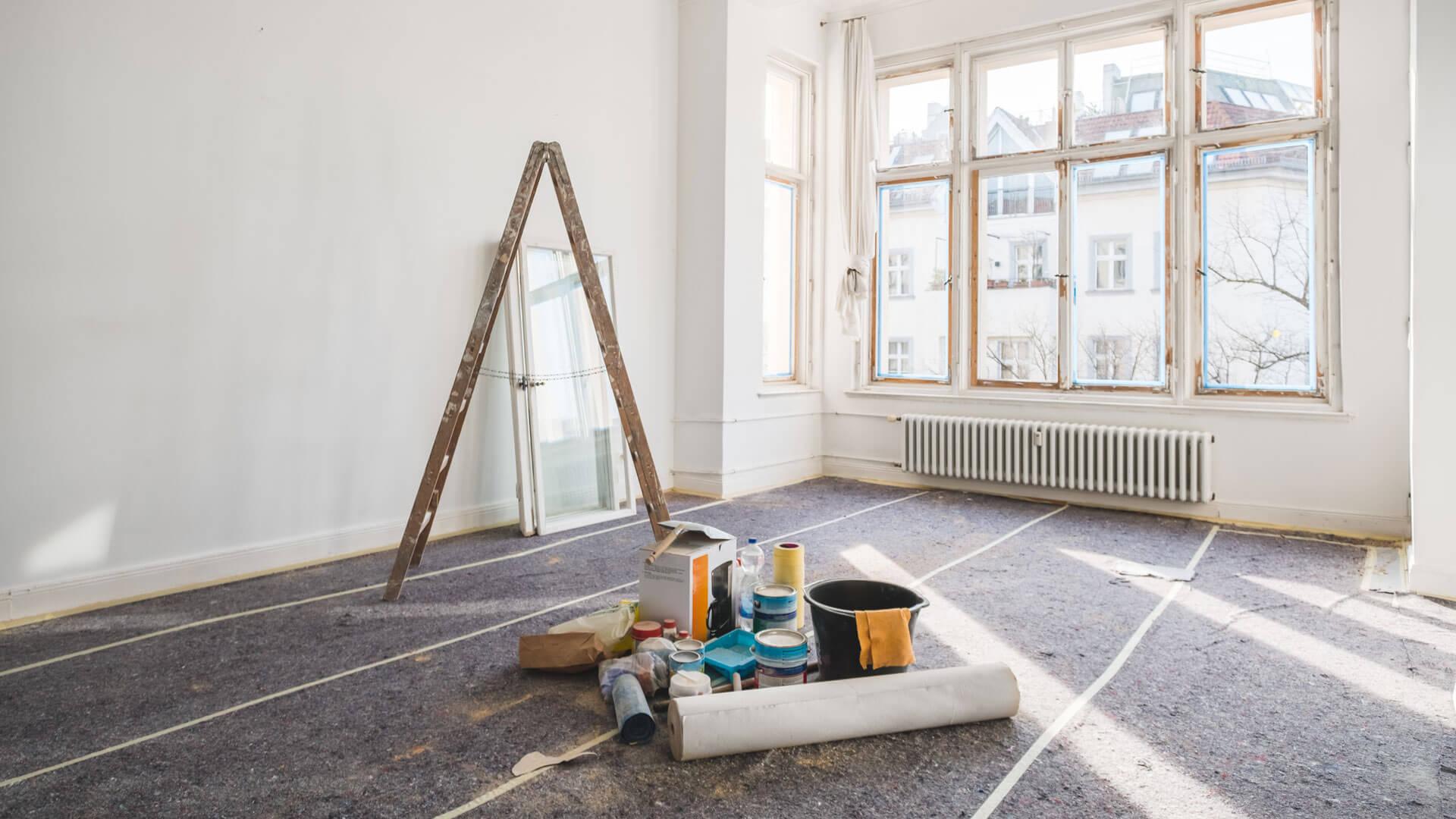 Ein Bild von einem Raum, der renoviert wird. Der Boden ist mit Vlies abgedeckt und in der Mitte des Raumes stehen eine Leiter, Eimer und Werkzeug.