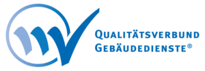 """Das Logo des Qualitätsverbund Gebäudedienste. Auf der linken Seite ist ein Kreis abgebildet mit zwei ansetzenden Strichen, die im dritten einen Haken in blau ergeben. Rechts davon ist in blau und Großbuchstaben die Aufschrift """"Qualitätsverbund Gebäudedienste"""" zu sehen."""