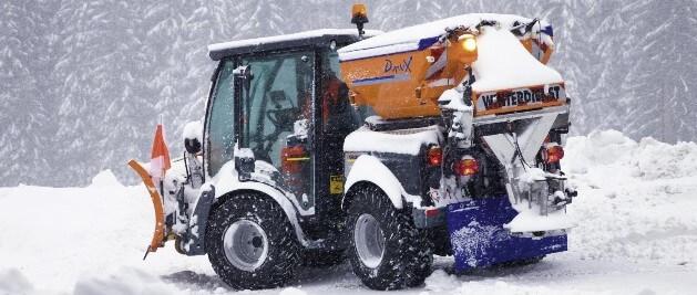 Im Schnee steht ein professionelles Räumfahrzeug, dass gerade einen Weg räumt, während es schneit.