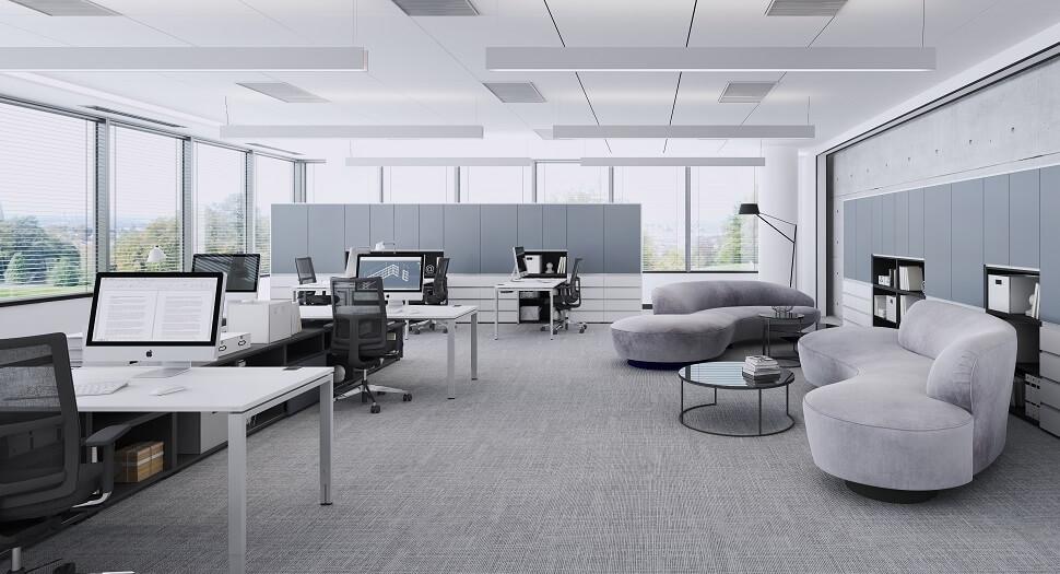 Ein Bild von einem Büroraum, in dem einige Schreibtische mit Monitoren stehen. An der rechten Wand befinden sich zwei graue Sofas mit einem kleinen Beistelltisch.
