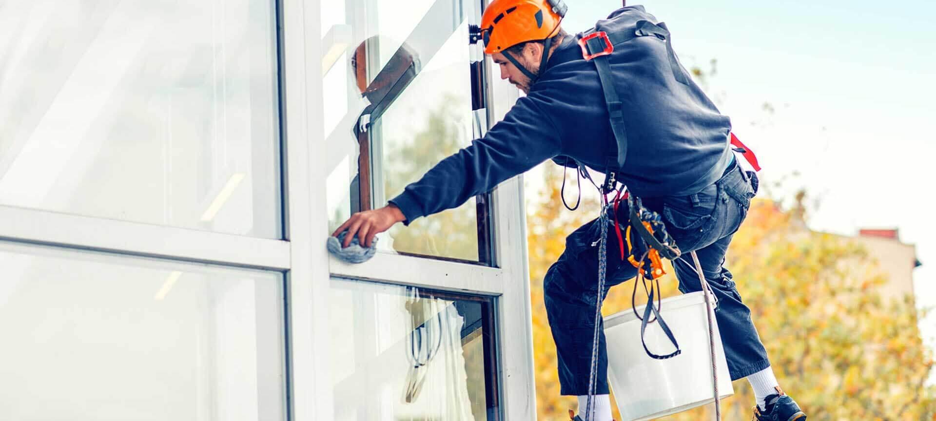 Ein Bildausschnitt eines Mannes, der mit Sicherheitsgurten in der Luft hängt und die Glasfassade eines Gebäudes von außen reinigt.