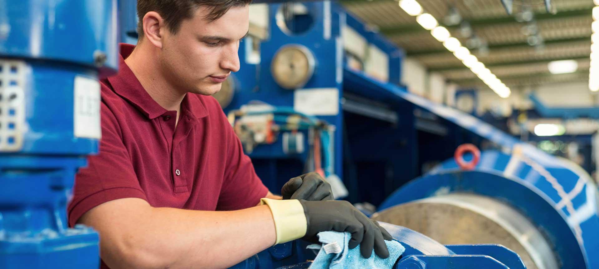 Ein schmaler Bildausschnitt von einem jungen Mann in einem roten Poloshirt, der Industriemaschinen reinigt.