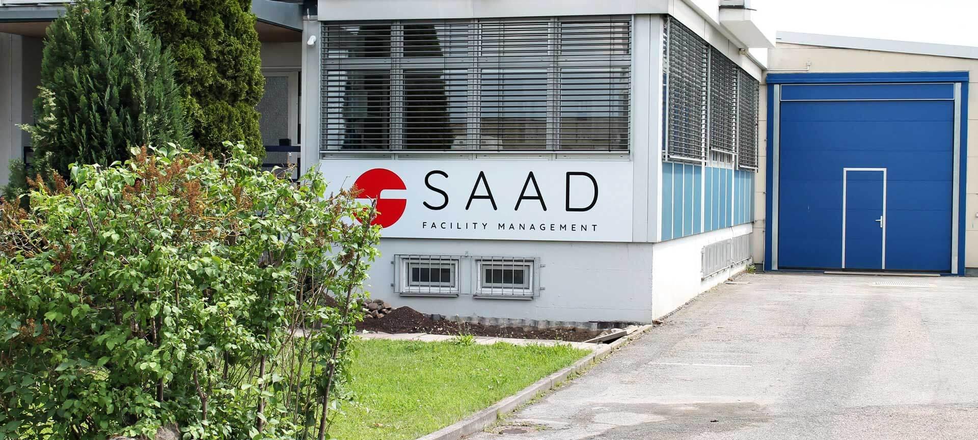 Ein Bildausschnitt des Firmengebäudes von SAAD mit einem blauen Garagentor im hinteren Gebäudeteil.